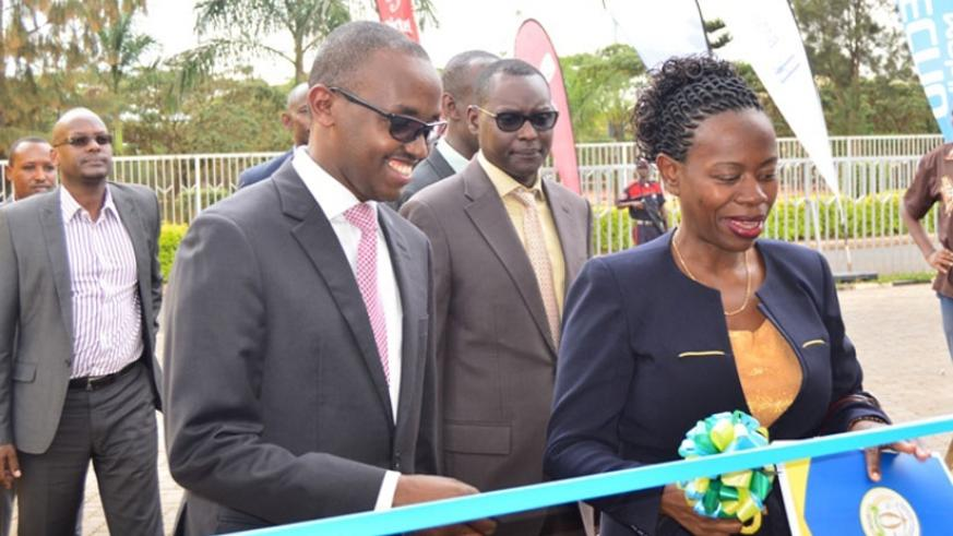 Nsanzabaganwa (R), flanked by Eric Rwigamba, the Ministry of Finance director general for financial sector development, cuts the tape to open the electronic and digital financial s....