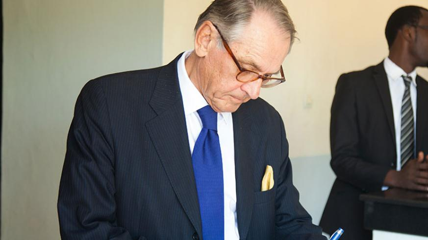 Eliasson writes in the visitors' book at Kigali Genocide Memorial Centre in Gisozi yesterday. (Nadege Imbabazi.)
