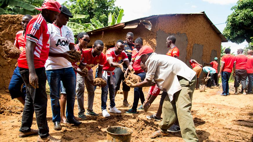 Members of the Manchester United fan club make bricks while others start works on the house (background) back in May. / Faustin Niyigena