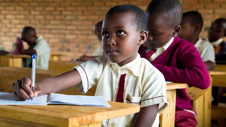 A pupil takes notes during class at Rusheshe Primary School in Kicukiro District. / Timothy Kisambira