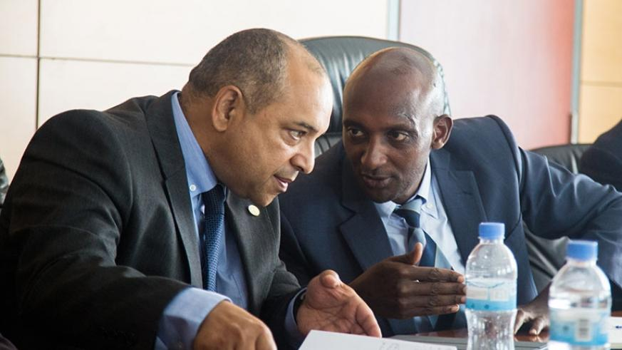 RRA  Commissioner-General Richard Tusabe (R) and  African Tax Admnistration Forum Executive Secretary Logan Wort compare notes at the meeting yesterday. (Photos by Faustin Niyigena)