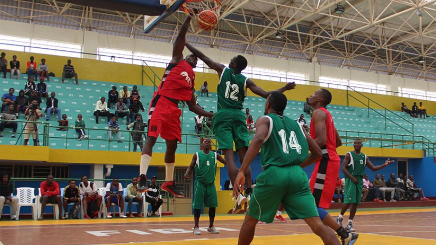 REG centre player Bievenue Ngandu goes for a slam as Rusizi players try to block him during third quarter on Sunday. REG won the game 93-65. / Courtesy