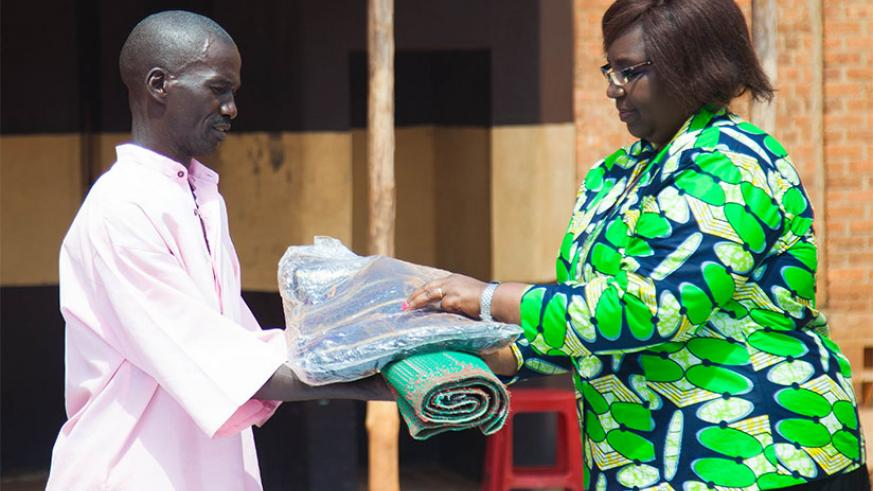 The Minister for Disaster Management and Refugee Affairs, Seraphine Mukantabana hands over relief items to an inmate at Nyarugenge Prison. The minister, who was handing over an ass....