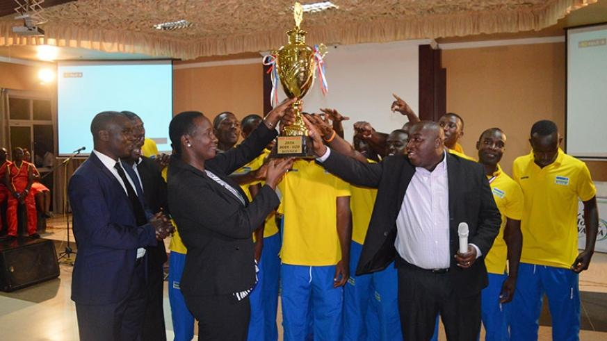 Sports and Culture Minister Julienne Uwacu (L) receieves the trophy that the national handball team won recently in Uganda (S. Ngendahimana)