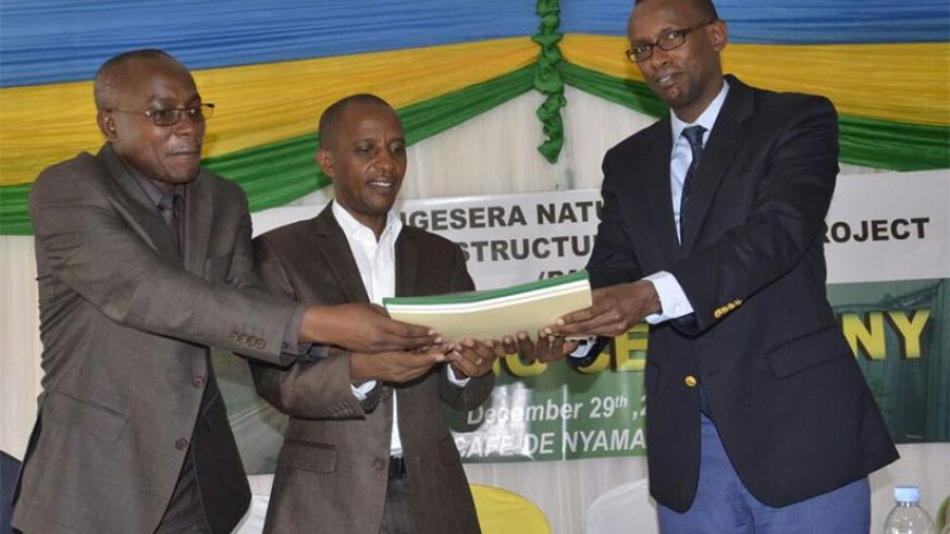 PS Kayisinga (R) and Dr Ngarambe (L) hand over the project file to Mayor Nsanzumuhire as a sign that the project activities now belong to the district. / Emmanuel Ntirenganya