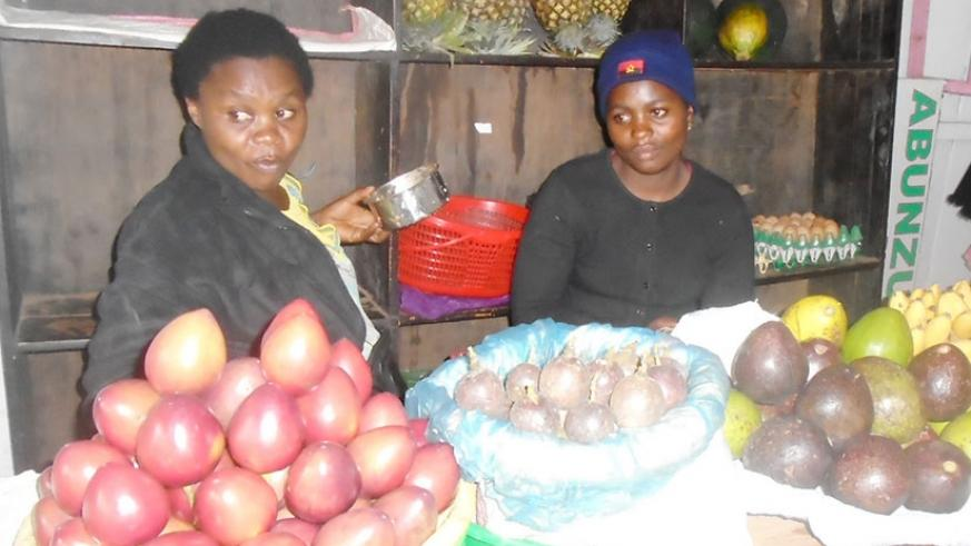 Aline Uwimana (Right) sells fruits at her stall in Kimironko market. (Photos by L. Atieno)