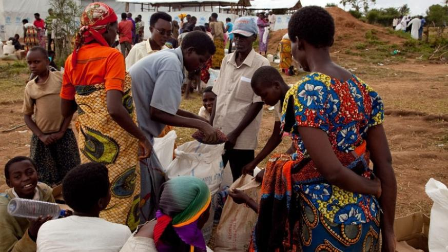 Burundian refugees receive food from World Food Programme officials in Mahama camp. The Ministry of Disaster Management and Refugees Affairs has urged refugees to start income gene....