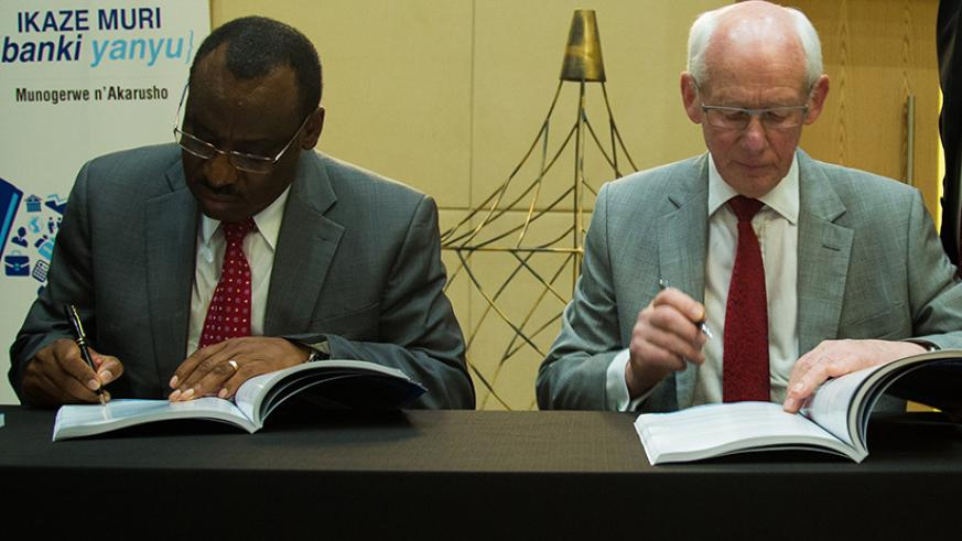 I&M Board Chairman Bill Irwin (right) signs IPO documents with Finance Minister Claver Gatete on Tuesday (Timothy Kisambira)