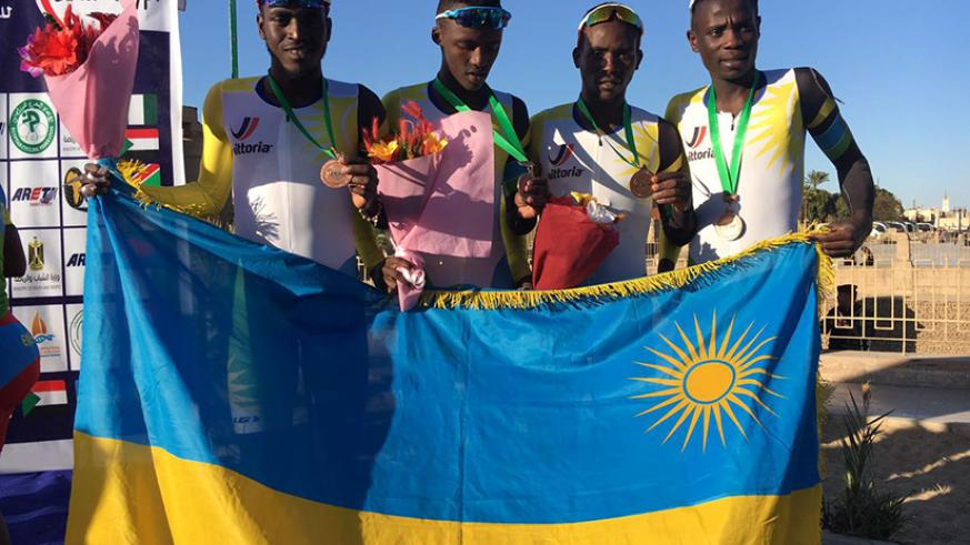 L-R: Valens Ndayisenga, Joseph Areruya, Samuel Mugisha and Jean Bosco Nsengimana pose with the national flag after winning the bronze medal in Team Time Trial on Tuesday. / Courtesy