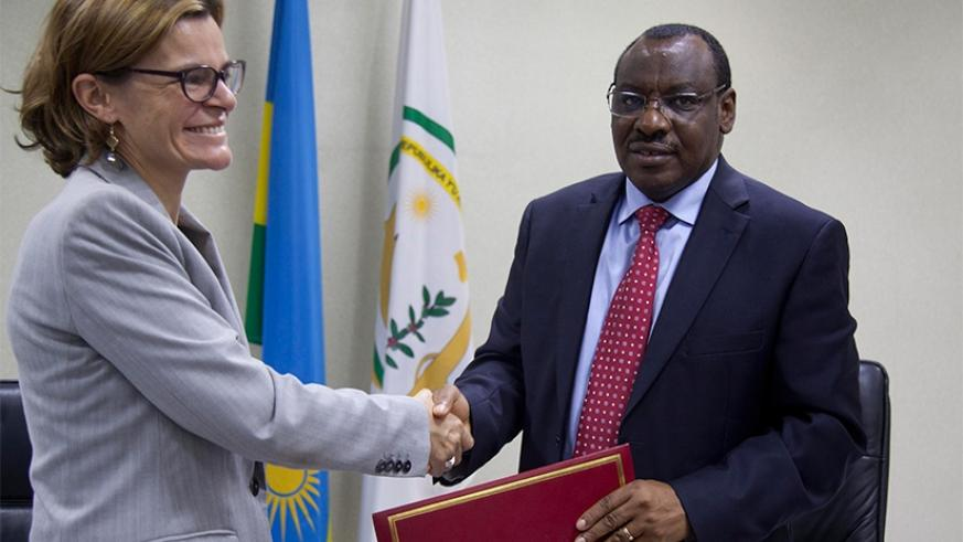 Beaufils (L) and Gatete exchange the MoU after the signing yesterday. Sam Ngendahimana.