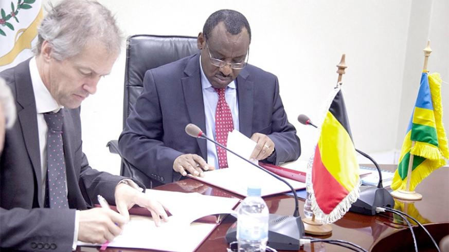 The Minister for Finance and Economic Planning, Claver Gatete (R) signs documents with Arnout Pauwels, the Belgium Ambassador to Rwanda, yesterday in Kigali. Sam Ngendahimana.