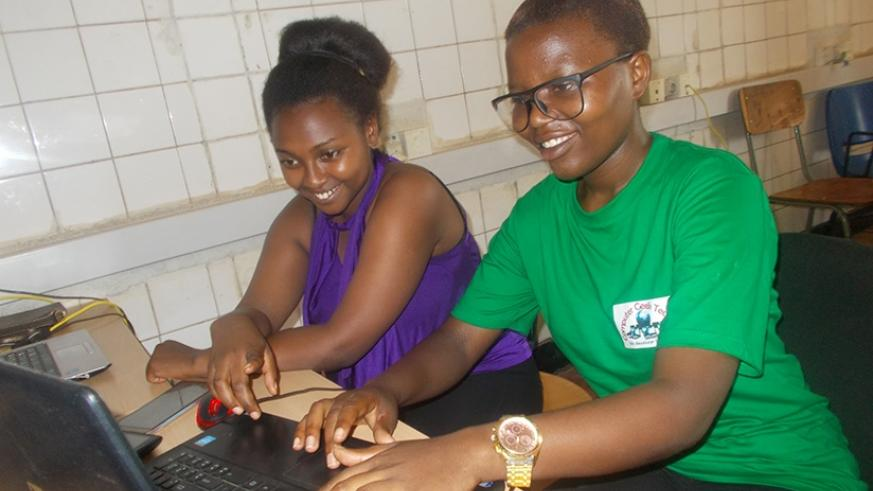 Ishemaryayo (R) and Immaculee Uwineza, a student at the College of Medecine and Health Sciences who is data manager of the platform, monitor their work. Elias Hakizimana.