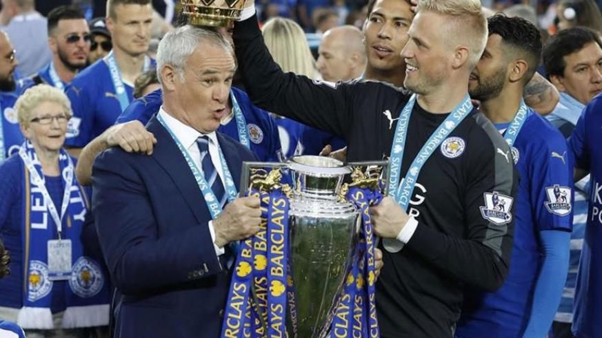 Leicester City manager Claudio Ranieri has the crown of the Premier League trophy placed on his head by goalkeeper Kasper Schmeichel as they celebrated becoming the English Premier....