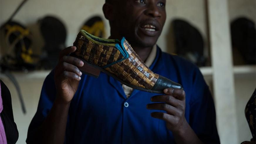 Hakizayezu displays one of the types of shoes he makes at Nyagatare-based factory. The businessman started off as a street shoe shine boy over 10 years ago. Below, a staffer puts f....