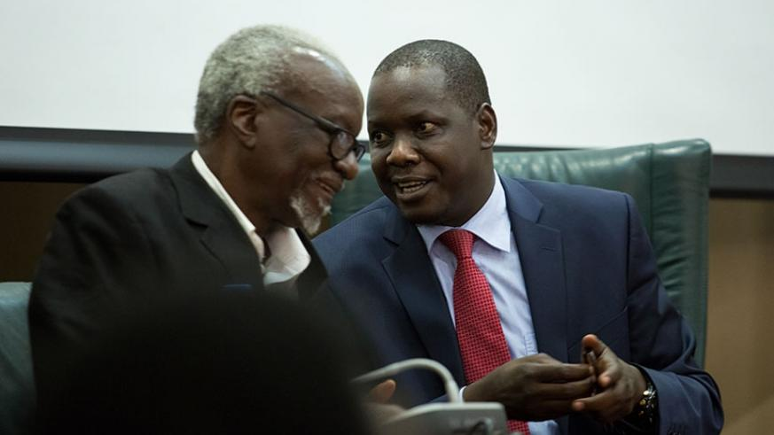 Kirunda Kivejinja, the Ugandan third deputy prime minister and minister for EAC Affairs (L), chats with Kidega during the news briefing in Kigali yesterday. Timothy Kisambira.