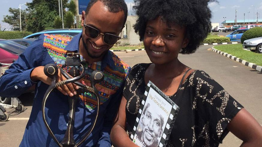 Dusabejambo with the Thomas Sankara prize while a friend admires the La Chance award plaque at Kigali International Airport shortly after her return from Burkina Faso.