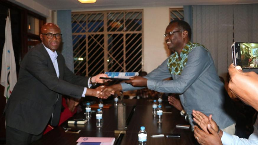Outgoing RNOSC president Bayigamba (R) officially hands over office to his successor Amb. Munyabagisha on Tuesday. / Jejje Muhinde