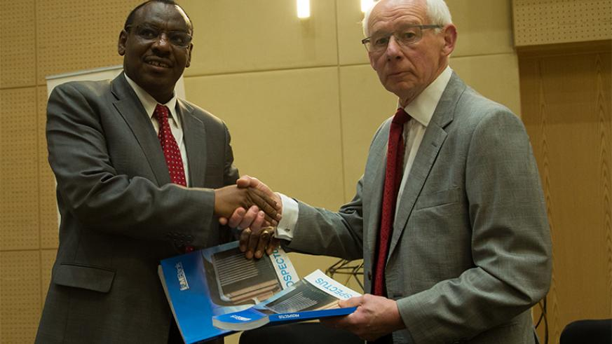 Finance and Economic Planning minister Claver Gatete exchanges documents with I&M Bank board chairperson Bill Irwin during the Initial Public Offering for the bank in Kigali last month.
