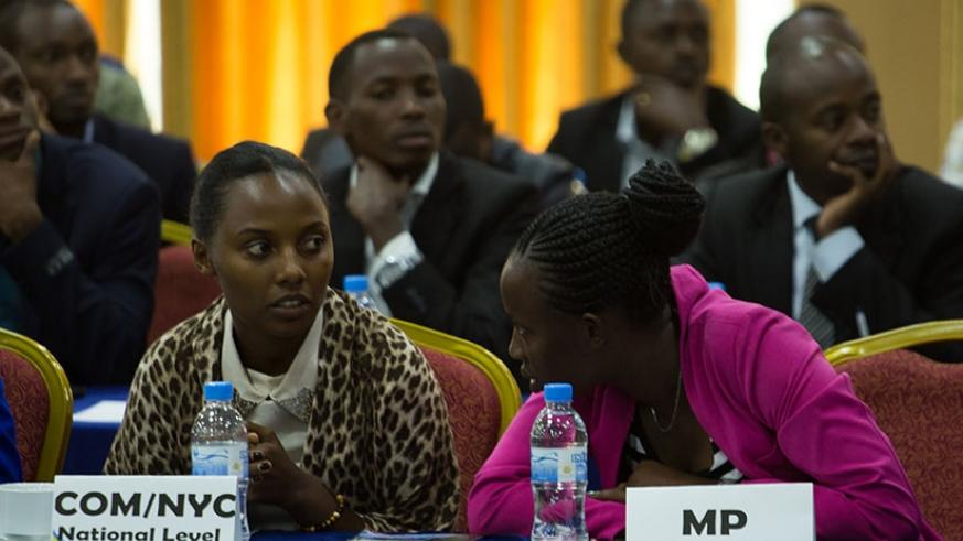 Justine Mukobwa, MP for the Youth at parliament (L) chats with Umutoni Chantal representative of high learning Institutions at the youth meeting. Timothy Kisambira
