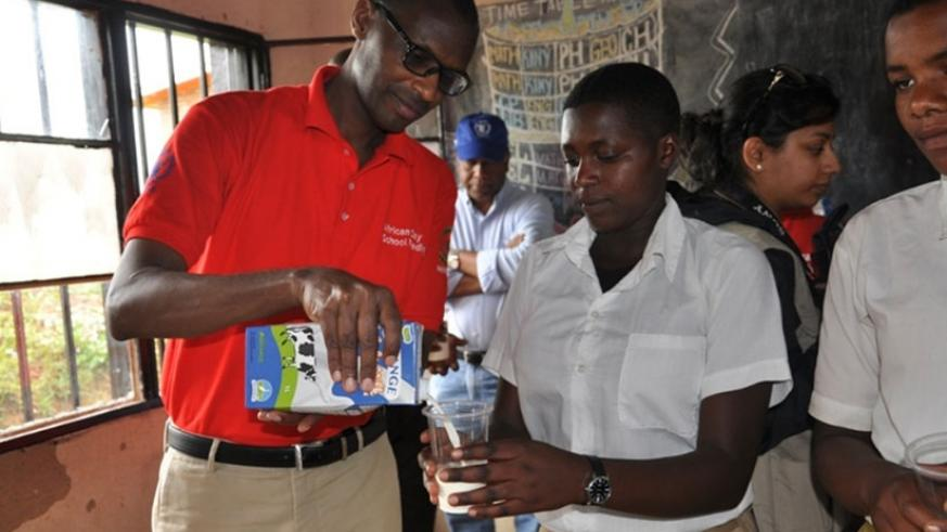Musafiri serves a student milk during the event in Nyamagabe. Julius Bizimungu.