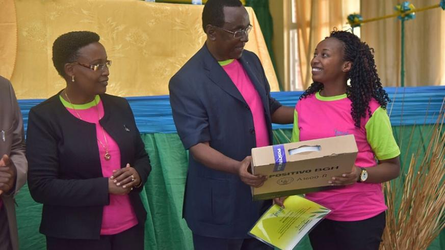 Makuza rewards one of the best performers as Amb. Jacqueline Mukangira, Board Member, Imbuto Foundation, looks on, in Rubavu District, yesterday.  Courtesy.