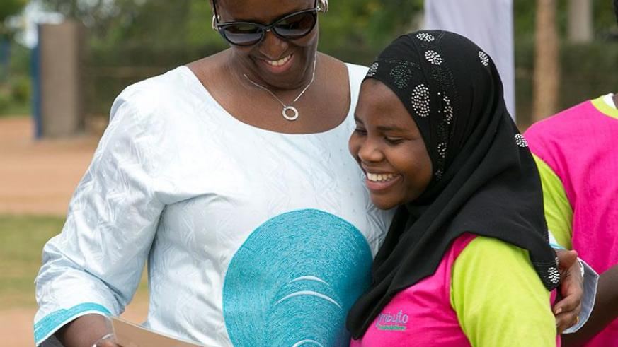 The First Lady, Mrs Jeannette Kagame, congratulates one of the best performing girls during the closing ceremony this year's Promotion of Girls Education Campaign in Mayange Sector....