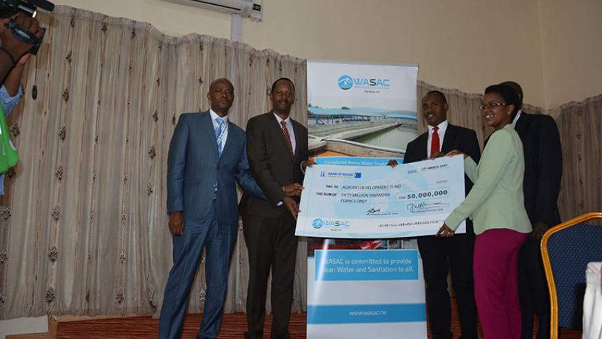 Water and Sanitation Corporation Ltd (WASAC) chief executive James Sano (second-right), together with the chairperson of WASAC Board, Gisele Umuhumuza (right), hands over a cheque ....