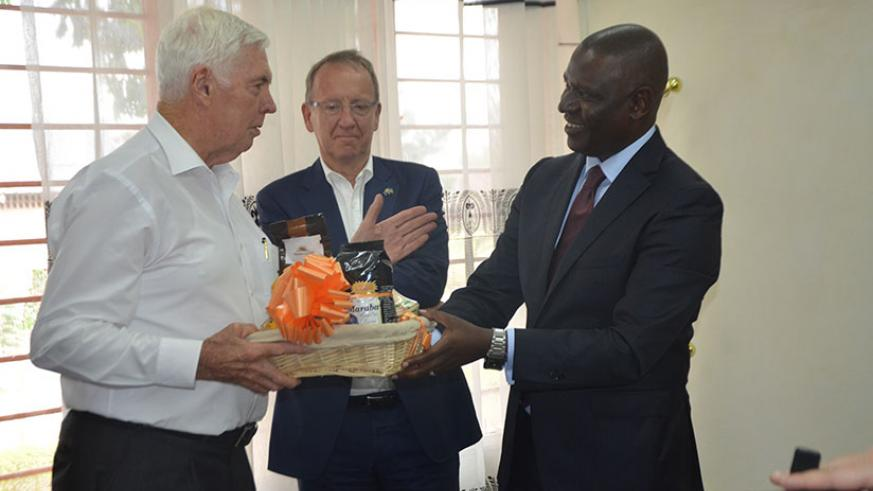 Gen. Michael Jeffery receiving some Rwanda products traded at international market from PSF Chairman Benjamin Gasamagera as Michael Roux the Honorary Consul General of Rwanda to Au....