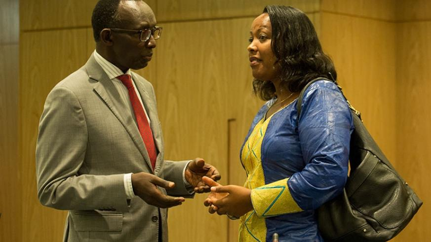 Chief Justice Sam Rugege (L) chats with the Minister for Gender and Family Promotion, Esperance Nyirasafari, after the opening of the meeting of judges and senior judiciary officia....