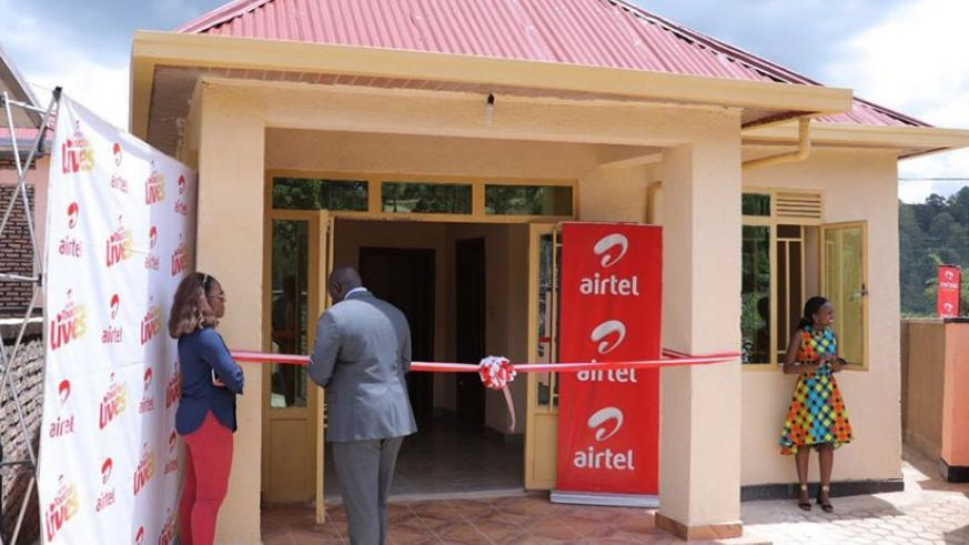 Kirungi (centre) cuts the tape as he unveils the house. (Courtesy photos)