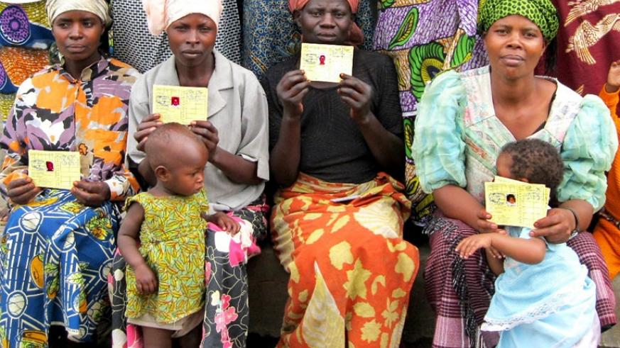 Mothers  show their medical Insurance (Mutuelle de Sante) cards. File.