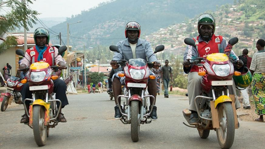 Tubanambazi (middle) and colleagues at work. The S6 dropout owns three moto taxis and is also the head of a motorcyclists group. / T.Kisambira.