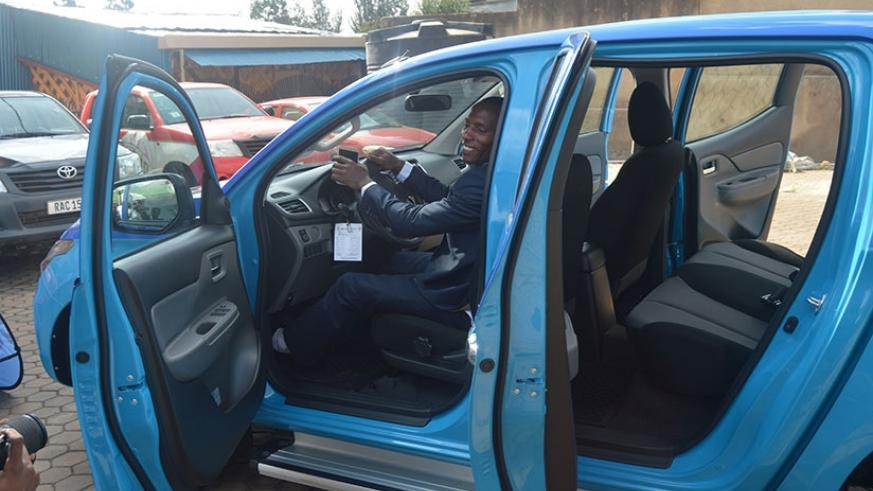 Francois Nsabimana poses in his brand new car. (Courtesy)