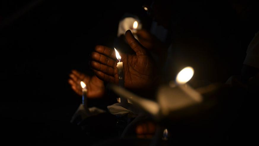Mourners hold lit candles during a night of remembrance at Kimihurura Sector in Kigali last year. / Sam Ngendahimana