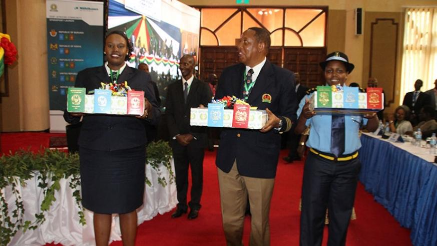 Immigration officials from the EAC Partner States display the EA passport during the 16th Ordinary Summit of the Heads of State and Government last year. Courtesy.