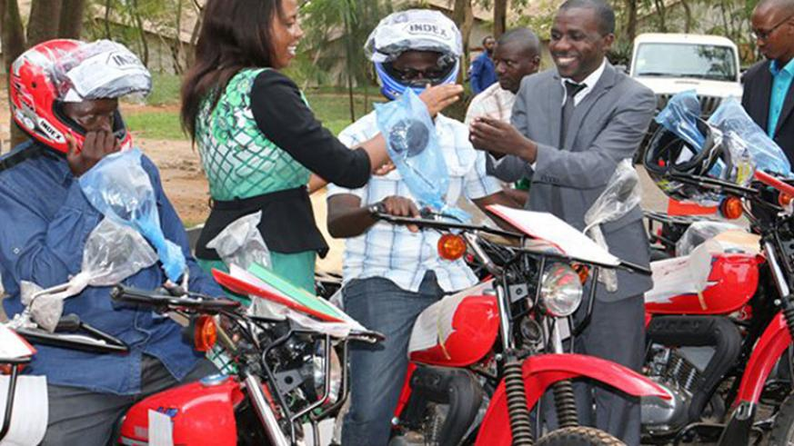 Urujeni (second left) hands over the motorcycles to some of the agronomists  last week in Kigali. The move seeks  to ease access to extension services by farmers. / Peterson Tumwebaze
