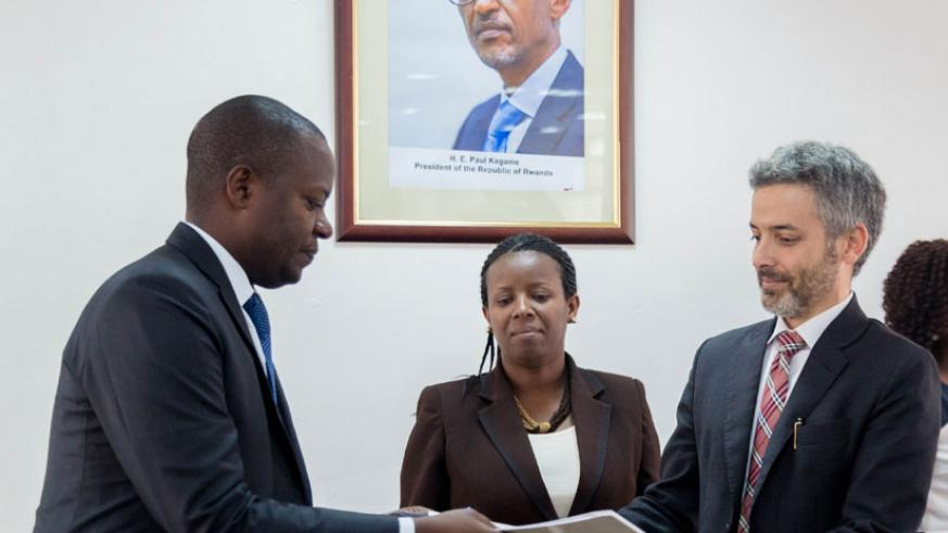Cohen exchanges documents with Emmanuel Kamanzi, the EDCL chief, in Kigali. / Courtesy