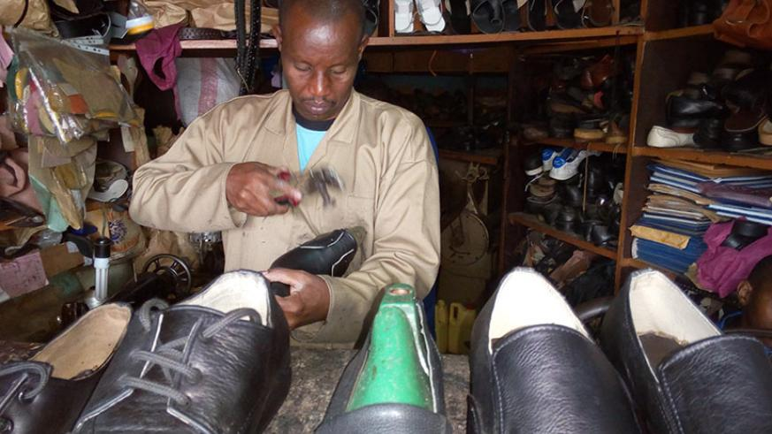 Bambanze putting final touches on a shoe at his workshop in Kigali. / Appolonia Uwanziga