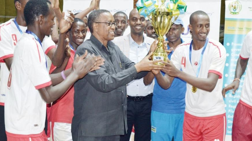 UNIK Vice Chancellor Prof. Silas Lwakabamba (C) lifts the Genocide Memorial Volleyball tournament trophy as players cheer on after winning it last year. (File)