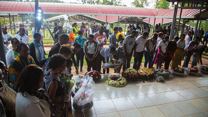 Relatives and friends of victims of the 1994 Genocide against the Tutsi lay wreaths on a grave at Nyanza Memorial Site on Tuesday. (All photos by Faustin Niyigena)