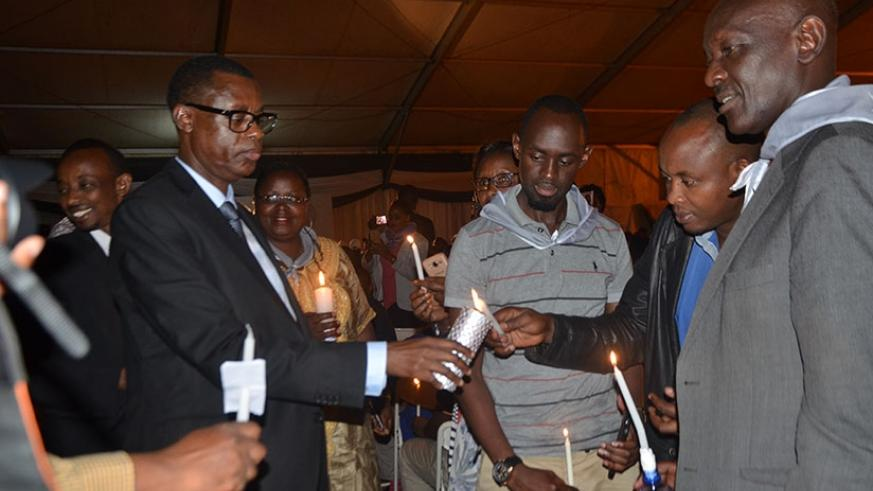 Minister Kabarebe (L) helps mourners light candles  in honour of  Genocide victims at Gikondo on Thursday. Courtesy.