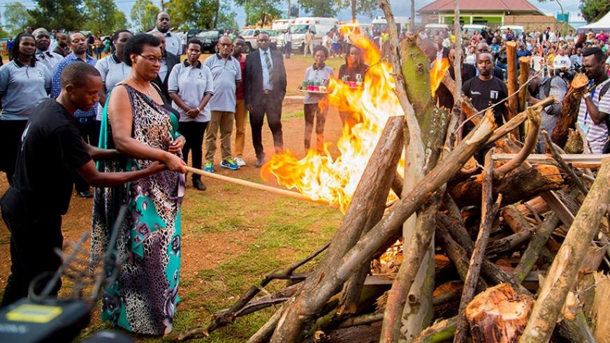 Speaker of Parliament Donatille Mukabalisa lights a fire at Nyanza memorial in Kicukiro, Tuesday night,  where mourners paid tribute to the thousands killed in the area following t....