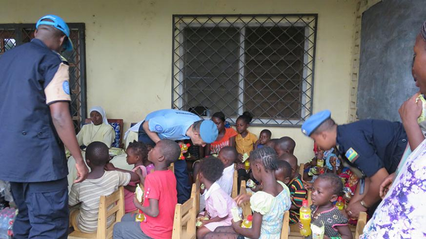 MINUSCA Police Commissioner and Rwandan peacekeepers feeding and interacting with the orphans. / Courtesy