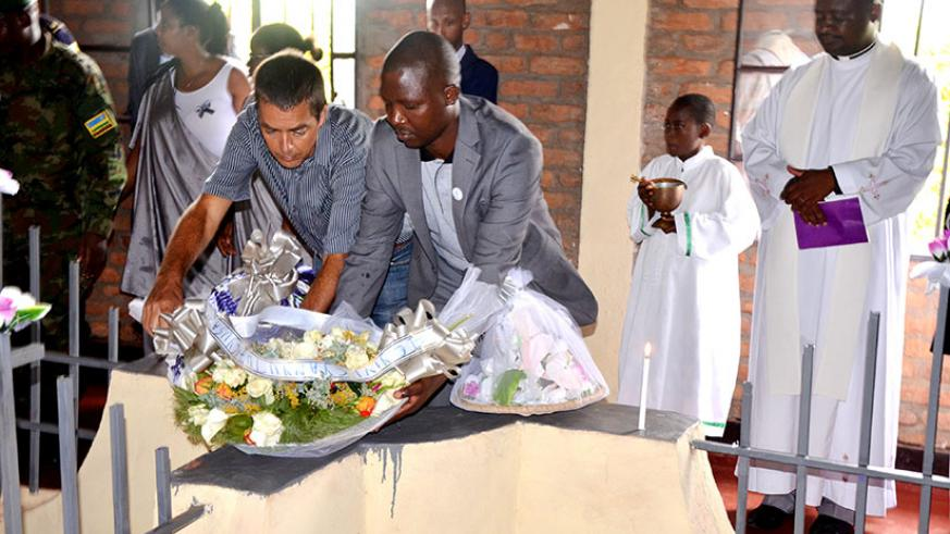 Willem Heese (L) and Mayor Nsigaye lay a wreath on the graves at Muganza Memorial site in Rusizi District. / Courtesy