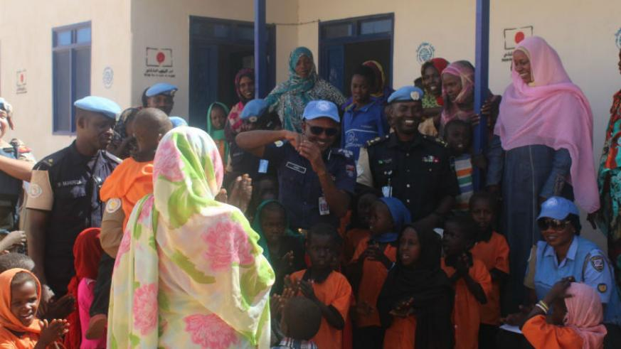 Rwanda police peacekeepers and UNAMID officials interacting with the women and children at the women centre block shortly after handing over the donation. / Courtesy