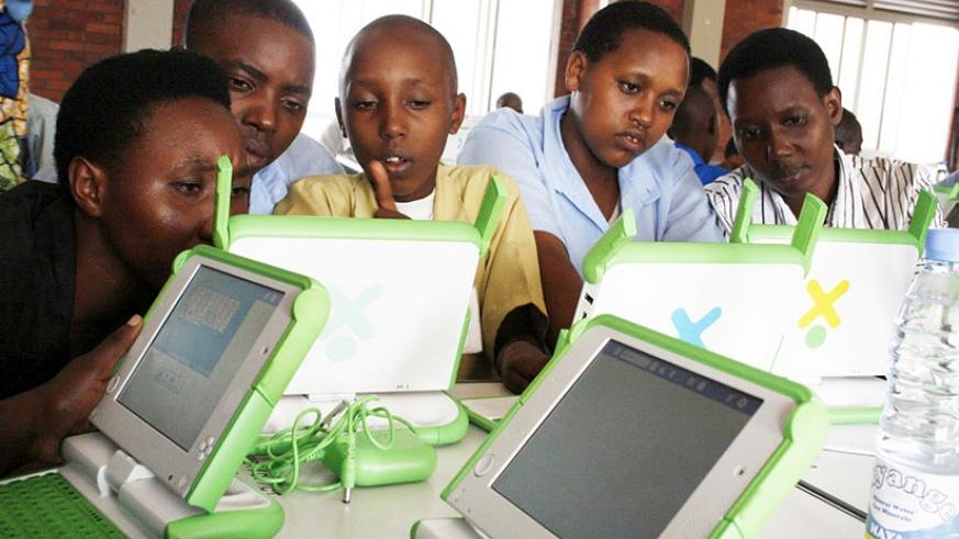 Pupils of Kimisagara Primary School use their laptops acquired under the One-Laptop-Per-Child project. (Timothy Kisambira)