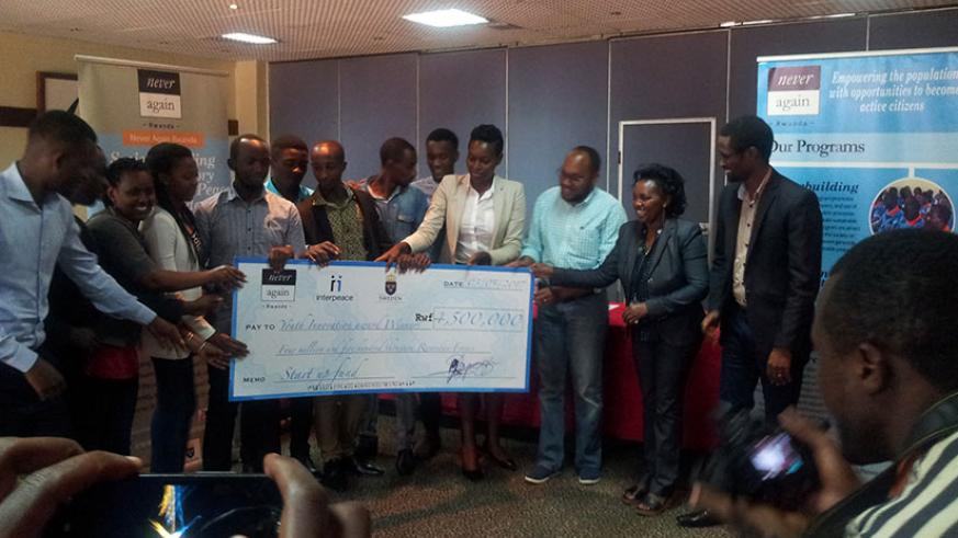 Heads of the nine youth associations that won cash prizes receive a dummy cheque on Wednesday in Kigali. / Eric Uwiringiyimana