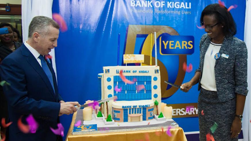 The CEO of Bank of Kigali Dr. Diane Karusisi (R) and the Chairman Marc Holtzman cut the giant cake designed in form of the BK Headquarters during the celebrations of it's 50th anniversary.