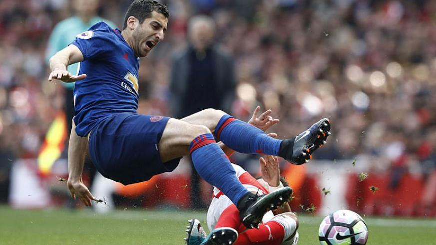 United's Henrikh Mkhitaryan is fouled by Arsenal's Alex Oxlade-Chamberlain during the first few minutes at the Emirates. Net photo