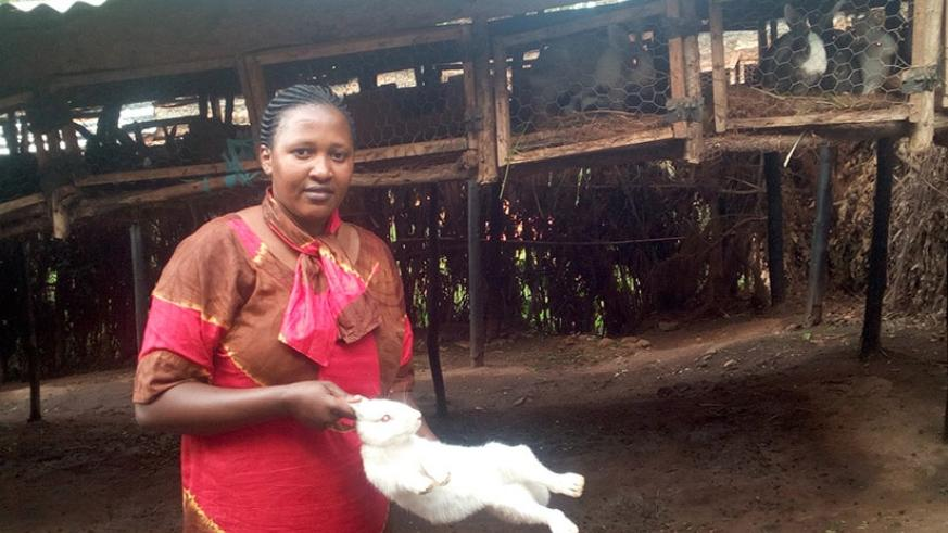 Mukandoli poses with one of her rabbits. The farmer has over 2000 rabbits.  (Photos: Remy Niyingize)